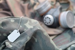 Dog tag with stalker soldiers soviet gas mask lies on green khaki camouflage jackets