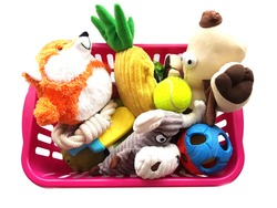 Dog toys. Plastic basket with balls, fox, dog, bull, pineapple Isolated on a white background.