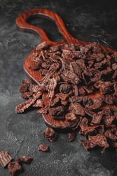 Dog treats. Dried pieces of lung on a dark stone background. Helpful treats for pets.