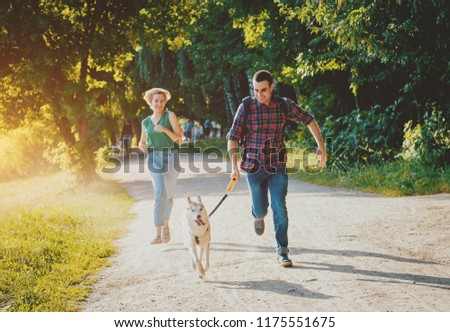Dog with owners spend a day at the park. Young couple and husky running, playing and having fun. Summertime background #1175551675