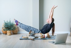 Doga or Doga yoga is the practice of yoga as exercise with dogs. Young woman in yoga position balancing with her dog. Home online training with a pet