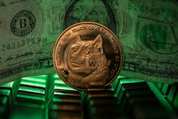 Doge cryptocurrency physical coin placed next to US dollar in the dark background and lit with green light