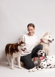 Dogs trainer, woman, among her three dogs, dalmatian and siberian husky isolated on white background. Trainer instructing dogs new teams. Dog training courses concept
