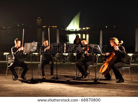 DOHA, QATAR - JANUARY 8: A string quartet performs against the backdrop of the Arabian Gulf and an Arab dhow as part of Qatar's celebration on hosting the Asian Cup, January 8, 2011 - stock photo