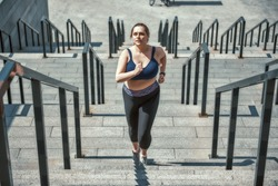 Doing all my best. Active plus size woman in sports clothing running up the stairs while exercising outdoors