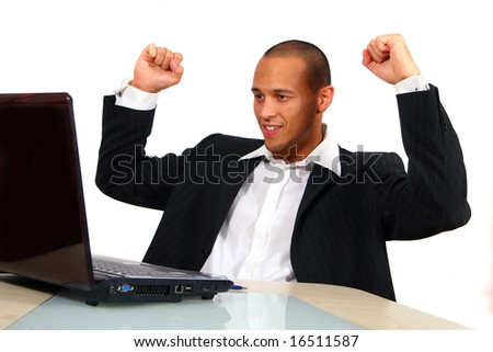 Doing Business A young satisfied businessman sitting in front of his laptop his hands in the air at the table celebrating his success. Isolated over white.