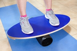 Doing exercises on balance board, person balancing and holding stability.