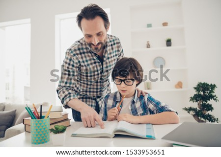 Doing home task with best daddy concept. Photo of two people positive patient intelligent daddy helping his offspring with homework preparation and tests