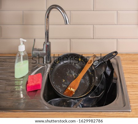Doing house chores. Huge pile of dirty dishes to wash. A pile of dirty dishes in a dirty sink