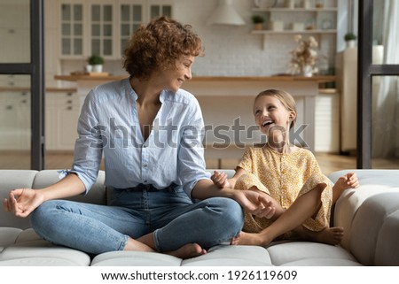 Doing like mommy. Laughing young mother little school age daughter having fun sit cross legged on couch at modern studio flat do yoga together. Funny small kid girl imitate mom in meditation practice