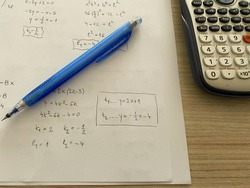 Doing math homework. Mathematics on white sheet, pen and calculator on the table.