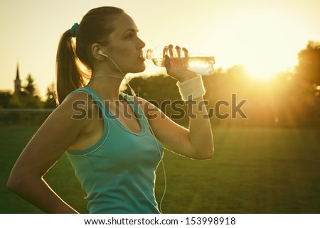 Doing Sport in the sunset Young woman drinking water after run