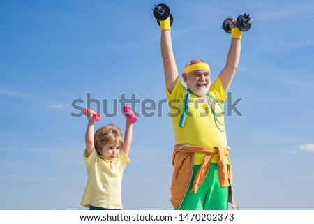 Doing sports is free.. Sport for little children. Sportsman grandfather and healthy kid with dumbbell exercise. Father and child training together