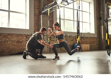 Doing squat exercise. Confident young personal trainer is showing slim athletic woman how to do squats with Trx fitness straps while training at gym. Stock fotó ©