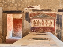 Dolias and fresco detai, of archaeological remains of Thermopolium of Vetutius Placidus, at Ruins of Pompeii. The city was an ancient Roman city destroyed by the volcano Vesuvius. Campania, Italy.