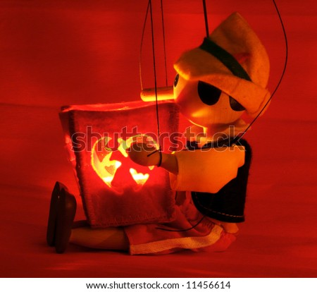 Doll and candle. Candles burn. Doll holds a candle. The red background. The game of light and shade. #11456614