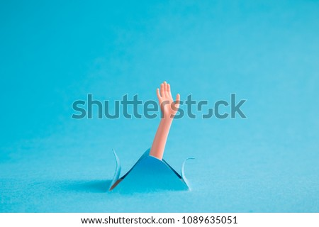 Doll arm emerging from blue paper background. Drowning minimal creative abstract concept.