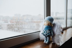 doll standing at the window, toy, baby cradle, girl, play, made with your own hands, creativity, windowsill, winter in the yard, glass, angel, white wings, blonde, stands on the Board interior item