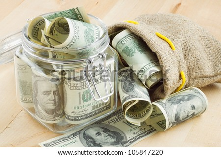 dollar banknote  in  glass jar and bag of money - stock photo