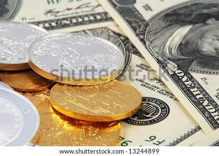 Dollar banknotes with a heap of golden and silver coins