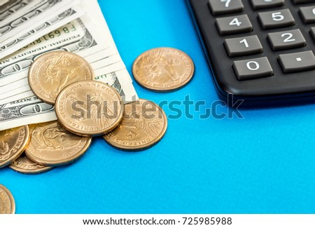 Dollar bills and coins with calculator on a blue background. Business background. Close up. #725985988