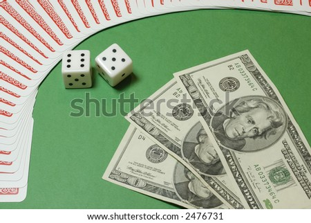 Dollar bills and gambling dices framed by playing cards on a casino table background
