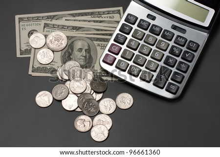 dollar bills, coins and a calculator on a gray background - stock photo
