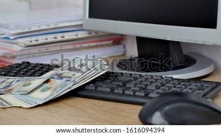 Dollar bills falling in heap on a wooden table in the office