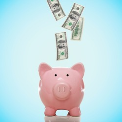 Dollar bills falling in or flying out of a pink piggy bank
