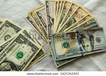 dollar bills of various denominations spread out on a flat surface as a background