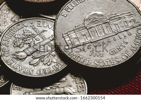 Photo of Dollar coins, Us Coins, American coins, Cents. Group of Coins on a table with red surface.