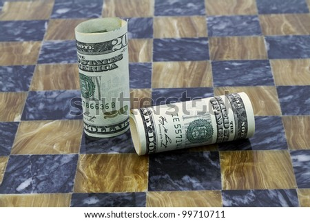 Dollar Game in Flux reflects financial instability or unevenness by marble pattern and placement of currency, one standing and one down.