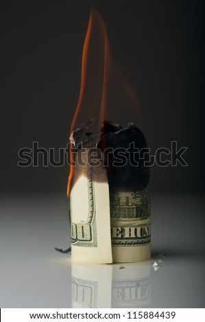 dollar note burning in fire on black background