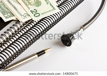 Dollar notes, pen and stethoscope lying on a doctor's desk