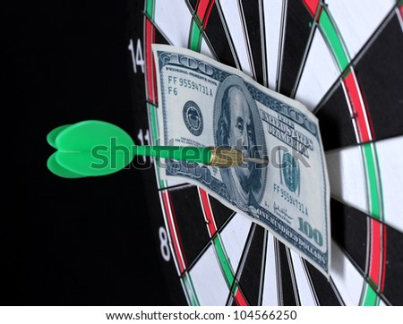 Dollar on bulls eye. Darts  close-up on black background