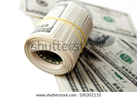 Dollar roll tightened with band on a background of dollars