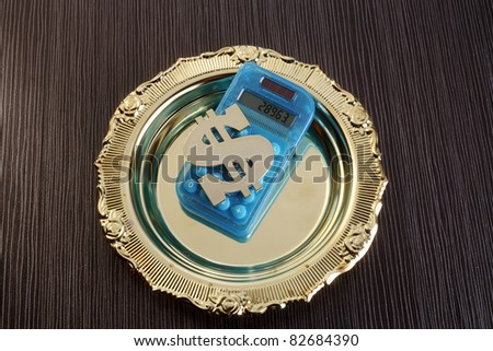 dollar sign and calculator on the plate