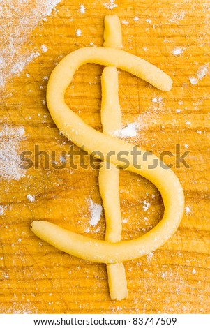 Dollar sign as christmas cookie made from raw dough