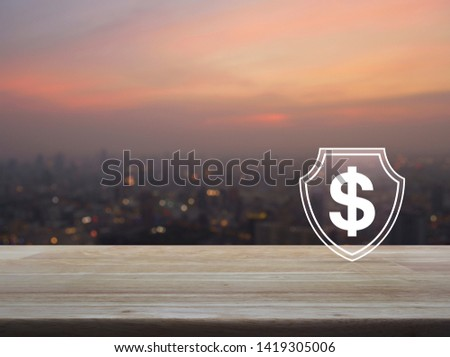 Dollar with shield flat icon on wooden table over blur of cityscape on warm light sundown, Business money insurance and protection concept #1419305006