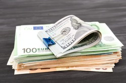 dollars and a stack of euros. Financial concept. A lot of money on a dark wooden background