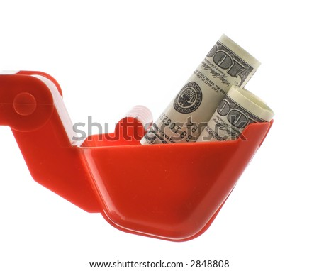Dollars bills within toy excavator bucket isolated over white background