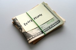 Dollars cash money and paper note with text written EXTRA INCOME on background - concept of financial planning - make more extra money from parttime side hustle or second job