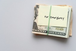 Dollars cash money and paper note with text written FOR EMERGENCY on copy space background - concept of financial planning saving money goal on purpose of rainy day crisis tough time