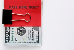 Dollars cash money clip with red note writing MAKE MORE MONEY , concept of earn more extra income from side job or side gig or start business to increase earning