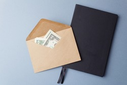 Dollars in an open paper envelope on a black notebook. An open envelope with banknotes on a table with a notebook on a gray background. International monetary currency. Close-up. Top view.