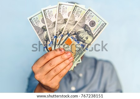 dollars in the hands. Businessman in blue shirt holding a 500 dollars. a fan of money