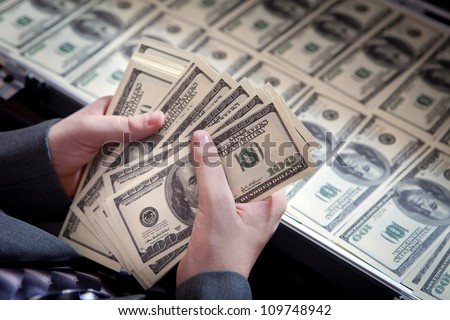 Dollars in the hands of a businessman. Suitcase with the dollars on the background.