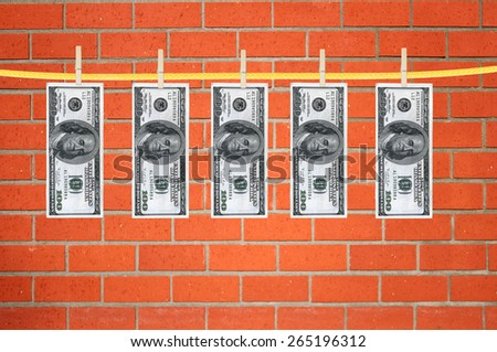 dollars laundering and dry after wash hang on clothespins over orange brick wall