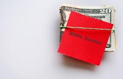 Dollars money cash in rubber band on copy space background ,with red note text typed EXTRA INCOME , concept of making side income or extra cash from second job to earn more in down economy