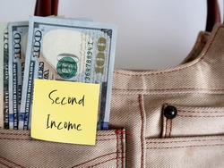 Dollars money in woman bag with sticky note SECOND INCOME ,concept of earn money from side hustle, side gig or part time job, side business to boost more income